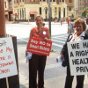 2 picketers in front of the Maryland Public Service Commission Building